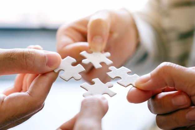Close-upbeeld van veel mensen die een stukje witte puzzel vasthouden en in elkaar zetten