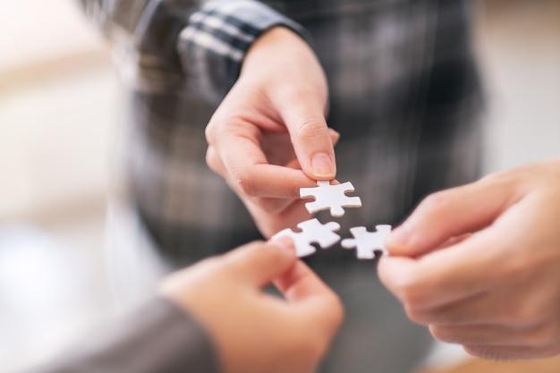 Close-upbeeld van veel mensenhanden die een stukje witte puzzel vasthouden en in elkaar zetten