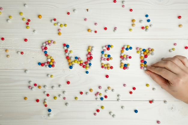 Close-upbeeld van vrouw die woord sweet maakt van kleurrijke snoepjes