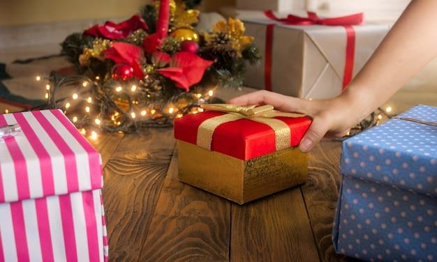 Close-upbeeld van vrouwelijke hand die rode giftdoos met gouden lint onder kerstboom zet