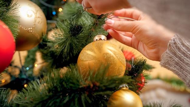 Close-upbeeld van vrouwelijke handen die mooie gouden bal op kerstboomtak hangen bij woonkamer