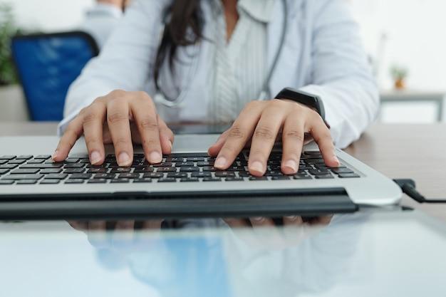 Close-upbeeld van vrouwelijke huisarts die aan computer werkt en patiëntengegevens en diagnose invoert
