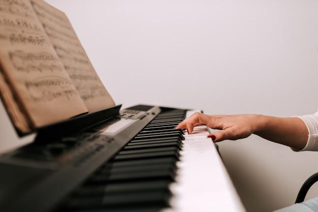 Close-upbeeld van vrouwelijke musicus het spelen piano van bladmuziek.