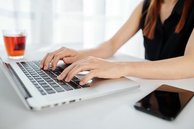 Close-upbeeld van vrouwelijke ondernemer die aan laptop bij bureau werkt en zwarte thee drinkt