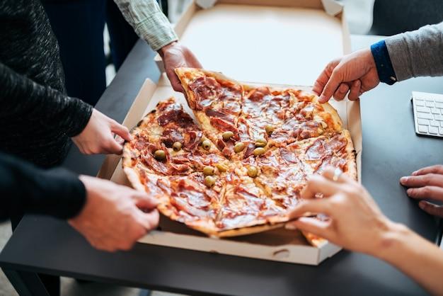 Close-upbeeld van zakenlui die pizza delen.