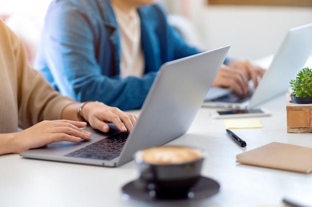 Close-upbeeld van zakenman die aan laptop computer samen in bureau gebruikt en werkt