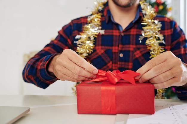 Close-upbeeld van zakenman die nieuwjaar uitpakt dat bij zijn bureau aanwezig is
