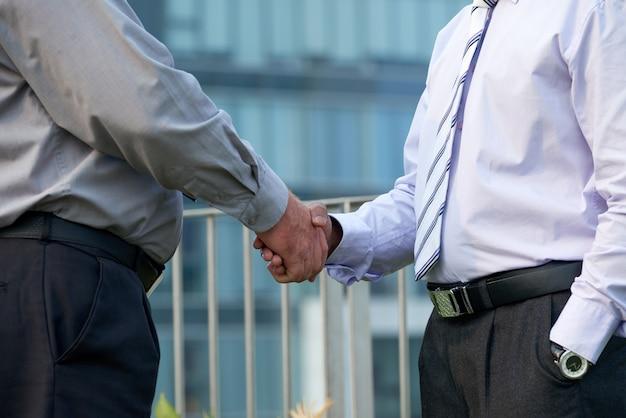 Close-upbeeld van zakenmensen in grijze en lavendelkleurige shirts die handen schudden