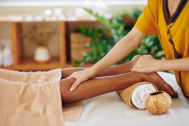 Close-upbeeld van zwarte jonge vrouw die ontspannende benenmassage krijgen in schoonheidssalon en druk met duim op kuitspier uitoefenen