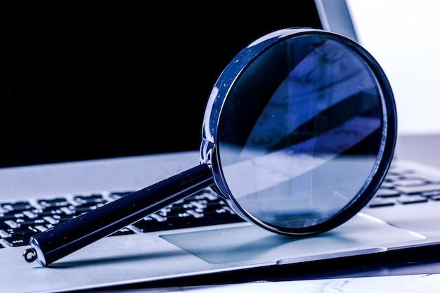 Close-upbeelden van vergrootglas op laptop toetsenbord