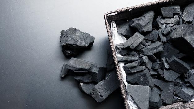 Close-upbeelden van zwarte kleurenhoutskool op zwarte achtergrond die van natuurlijk hout is gemaakt