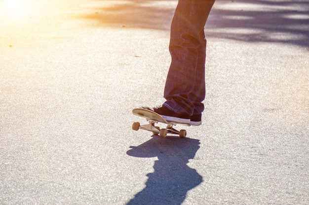 Close-upbenen van tiener die een skateboard op de weg van het openbare park spelen.