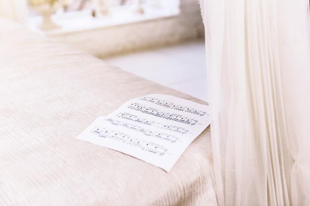 Close-upblad met muzieknoten die op het bed liggen