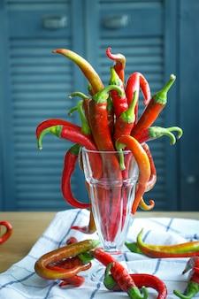 Close-upboeket van lange rode spaanse peperpeper in een uitstekende glasdrinkbeker op een natuurlijk tafelkleed