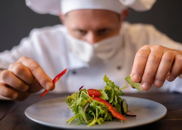 Close-upchef-kok die met masker schotel voorbereidt