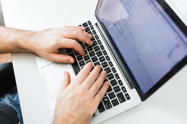 Close-upcodering op scherm, man handen die html en programmering coderen