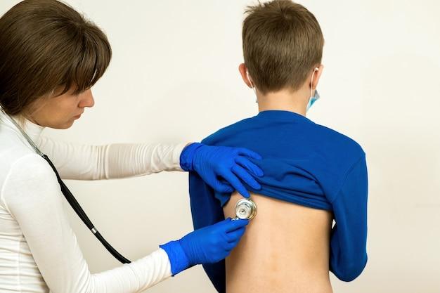 Close-updetail van artsenhand die ziek kind met stethoscoop onderzoeken.