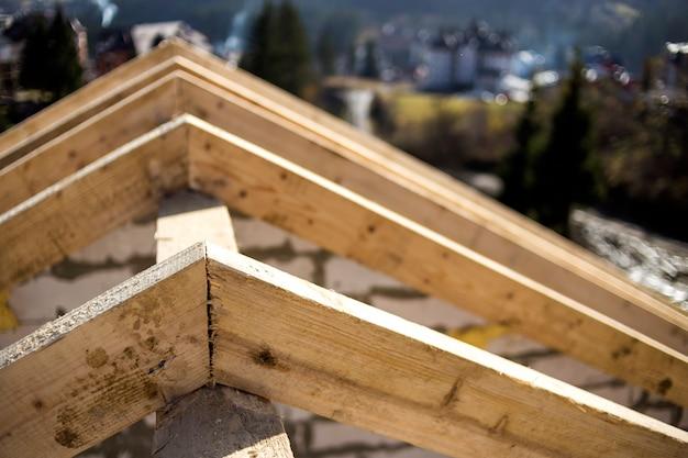Close-updetail van dakframe van ruwe houten timmerhoutbalken op achtergrond van nevelig berglandschap op ecologisch gebied. bouwen, dakbedekking, constructie en renovatie concept.