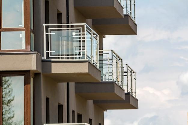Close-updetail van flatgebouwmuur met balkons en glanzende vensters op blauwe hemelachtergrond.