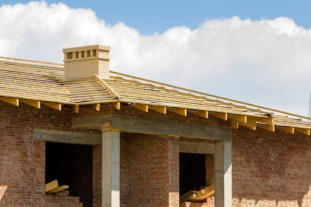 Close-updetail van houten dak van nieuw baksteenhuis met twee witte schoorstenen in aanbouw. houtkader van natuurlijke materialen tegen heldere hemel. professioneel bouw- en wederopbouwconcept.