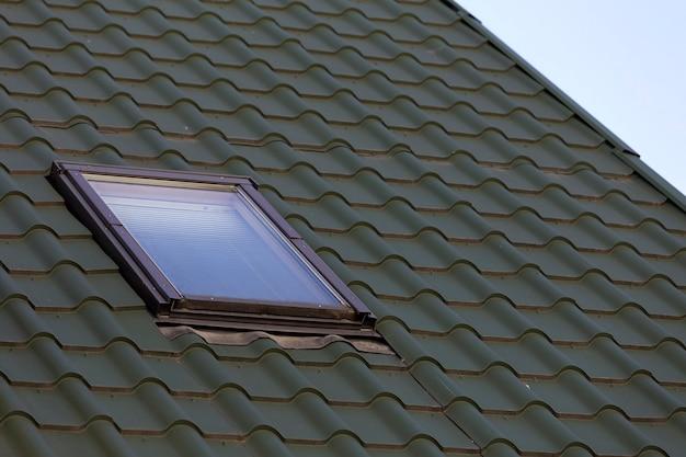 Close-updetail van nieuw klein zolder plastic venster dat in donkergroen shingled huisdak wordt geïnstalleerd