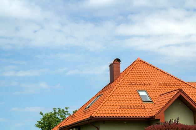 Close-updetail van nieuwe moderne huisbovenkant met shingled rood dak, hoge schoorsteen, zoldervensters op duidelijke blauwe hemel