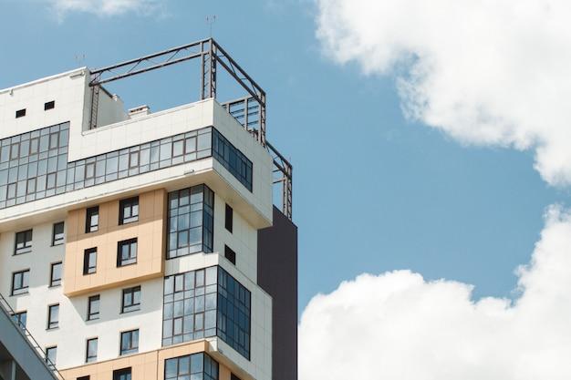 Close-updetail van nieuwe witte flatgebouwen met terrasvormige balkons tegen de blauwe hemel.