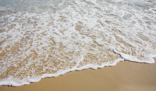 Close-updetails van kleine oceaangolven die aan wal op het strand waait