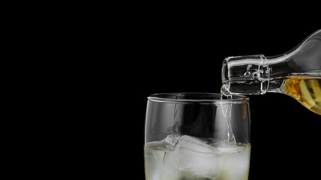 Close-updrank het gieten in glas met ijsblokjes
