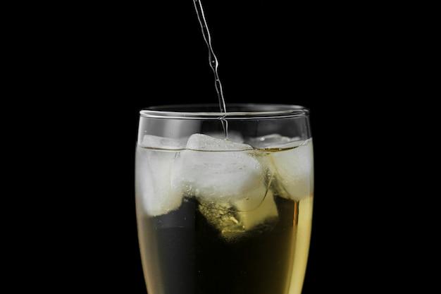 Close-updrank het gieten in glas met zwarte achtergrond