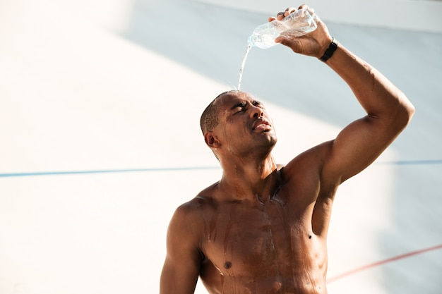 Close-upfoto die van de jonge afrikaanse sportenmens water op zijn hoofd uitgieten, die na training rusten
