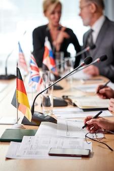 Close-upfoto, focus op microfoons, mensen uit het bedrijfsleven zitten voor microfoons tijdens deelname aan persconferentie