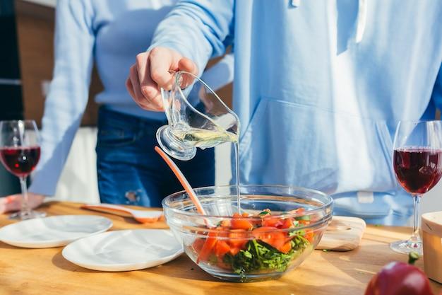 Close-upfoto, handen gesneden groenten in salade