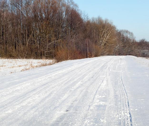 Close-upfoto's van voertuigbandensporen in de sneeuw
