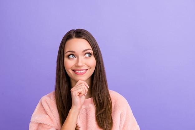 Close-upfoto van aantrekkelijke dame die dromerige lege ruimte op paarse muur kijkt