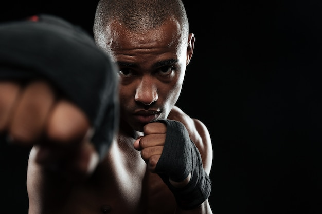 Close-upfoto van afro-amerikaanse bokser, die zijn vuisten toont