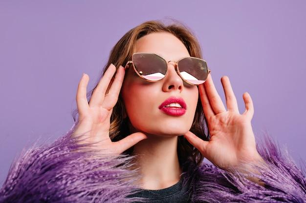 Close-upfoto van betoverende jonge vrouw met trendy make-up die met verbazing omhoog kijkt