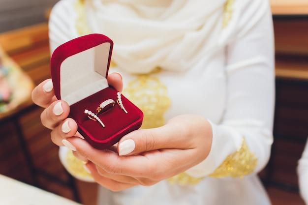 Close-upfoto van bruid en bruidegomholdingsdoos met gouden ringen.