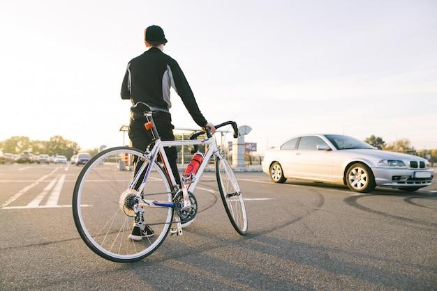 Close-upfoto van de benen van de fietser die een fiets op de achtergrond van de zonsondergang trekt.