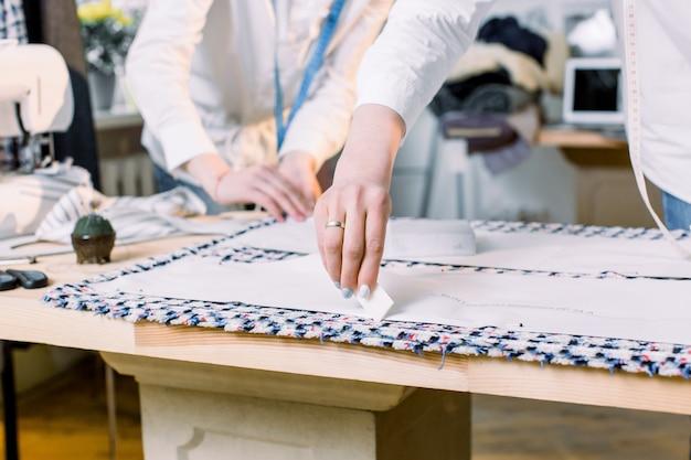 Close-upfoto van de handen van vrouwen van naaister die met naaiende patronen werken. kleermaker op het werk, lijn tekenen op stof met krijt