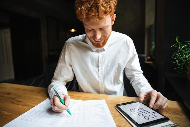 Close-upfoto van de knappe readhead gebaarde mens in wit overhemd, die terwijl thuis het werken glimlachen