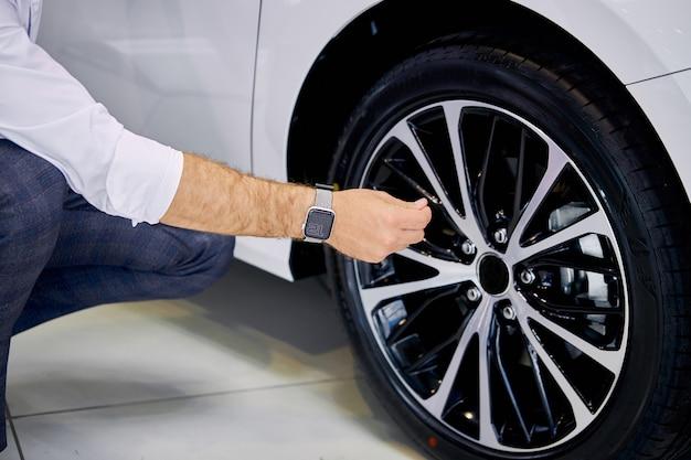 Close-upfoto van de mens die autowielen in de dealer controleert