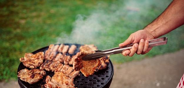 Close-upfoto van de mens die vlees op barbecue roosteren