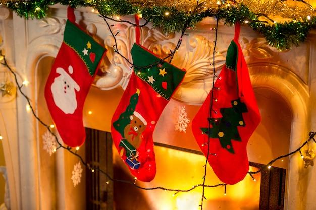 Close-upfoto van drie rode kerstsokken die aan een brandende open haard hangen