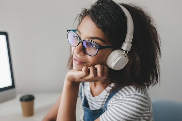 Close-upfoto van dromerig meisje met lichtbruine huid die aan iets aangenaams denken terwijl ze van muziek geniet