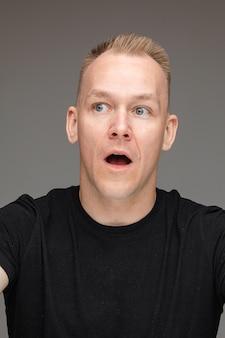 Close-upfoto van een blonde man die van verbazing zijn mond opent