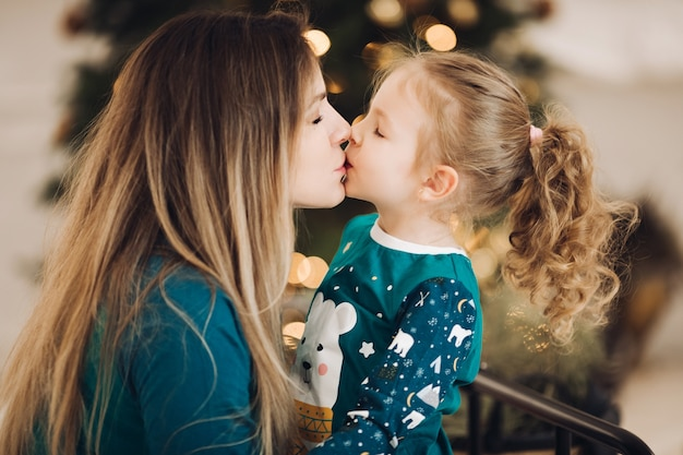Close-upfoto van een donkerbruine dame die een klein meisje kust met de kerstboom. concept vakantie