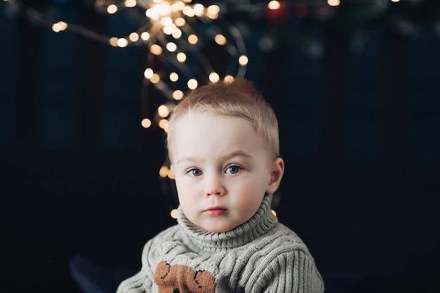 Close-upfoto van een ernstige kleine jongen met kerstverlichting op de achtergrond