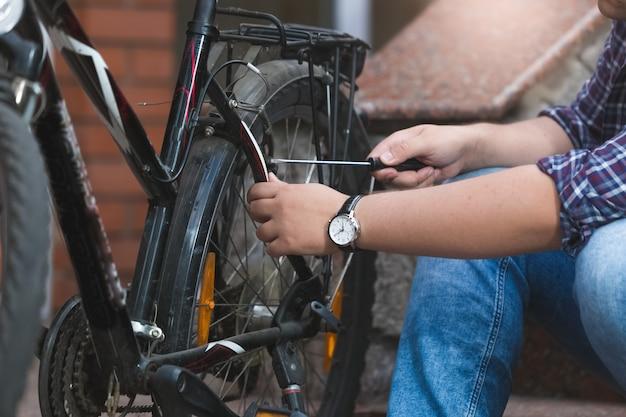 Close-upfoto van een jonge man die het achterwiel van een fiets repareert