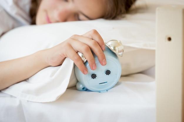 Close-upfoto van een jonge vrouw die de wekker vasthoudt en uitzet